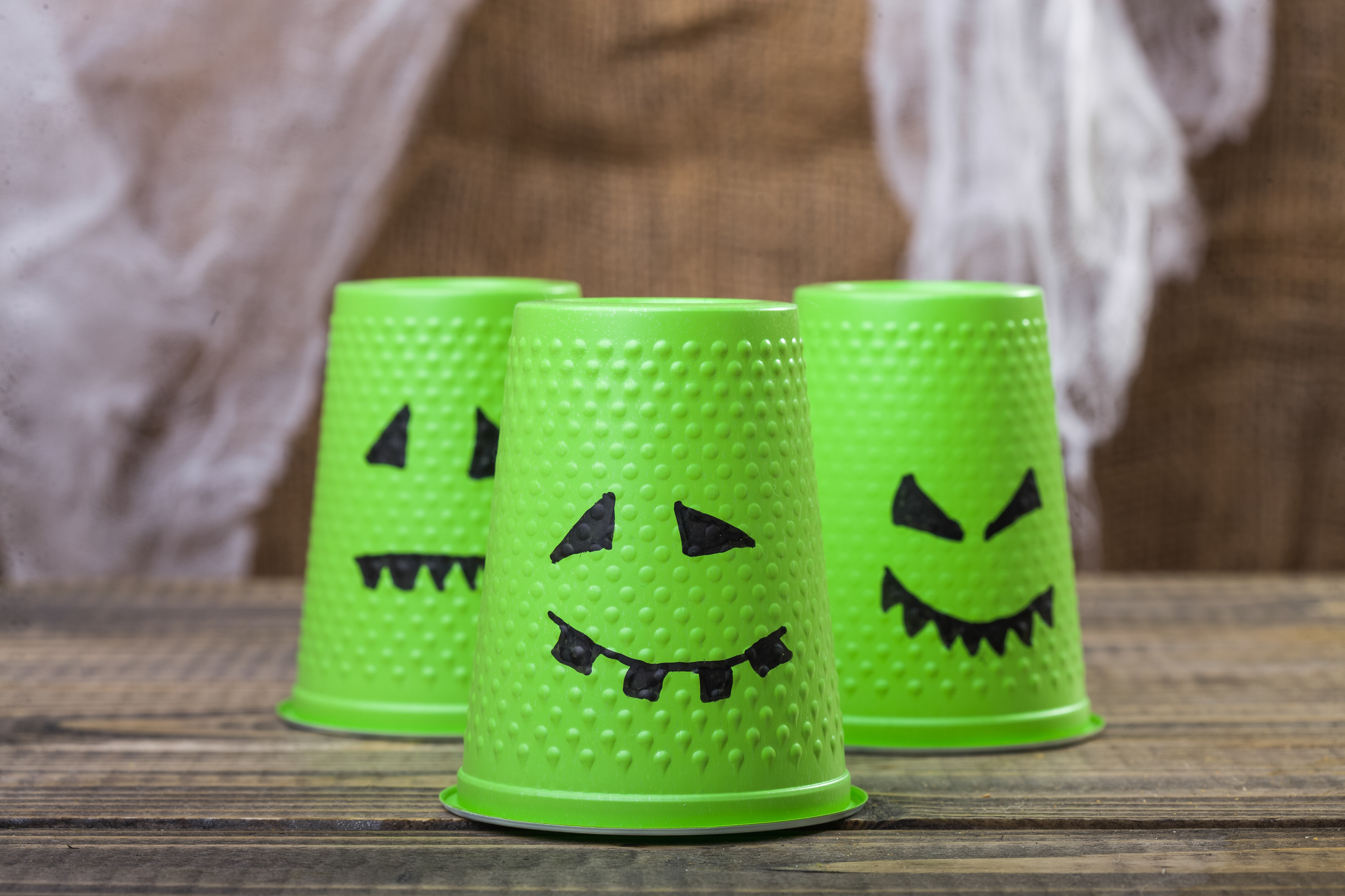 Photo set of three green disposable cups with Halloween ghost scary faces smiles with teeth drawn in black felt pen standing on wooden table over blurred rustic background horizontal picture