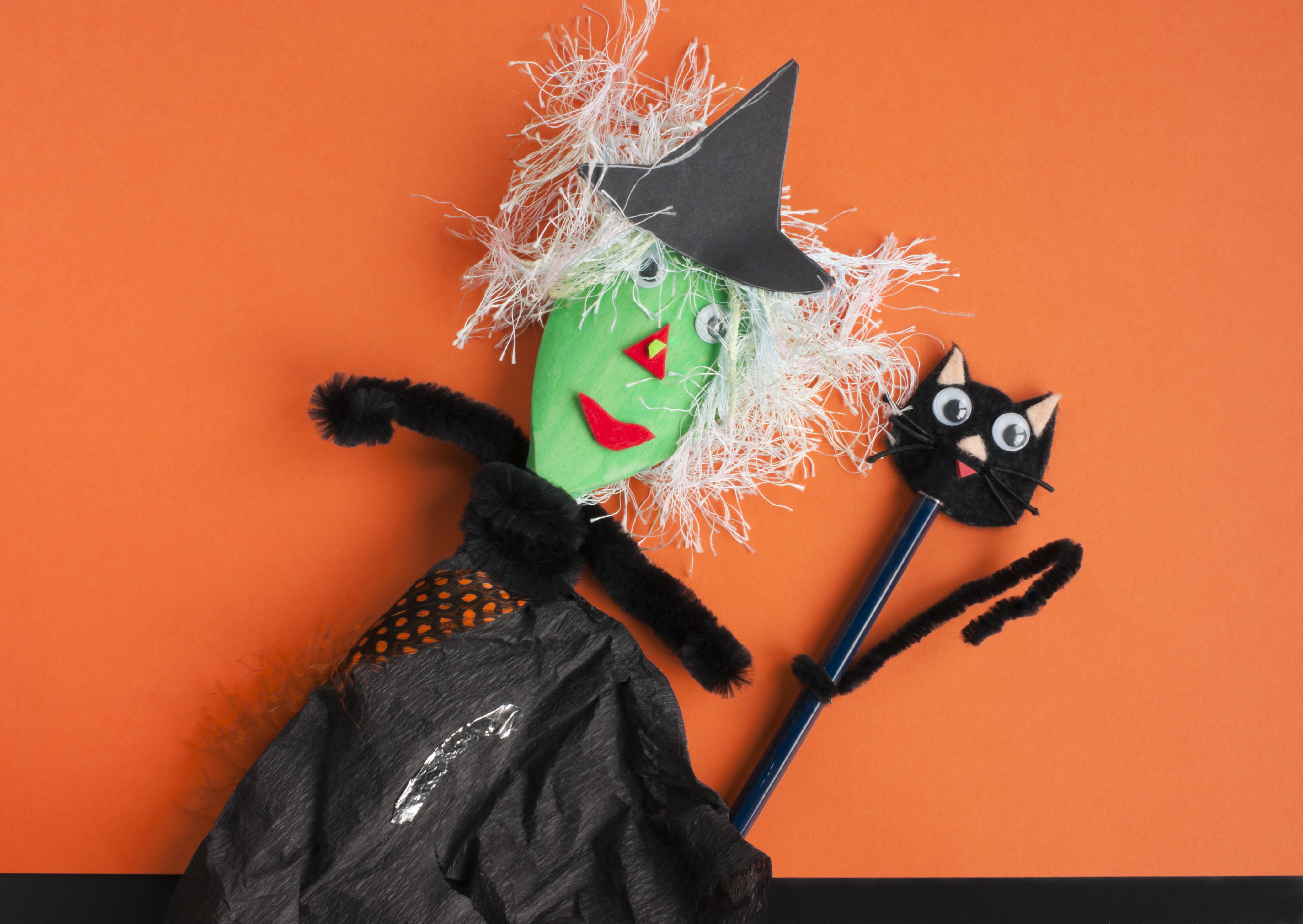 Halloween toys. Witch made of a wooden spoon tissue paper and pipe cleaners and a cat made of an old pencil and pipe cleaners. Concept for Halloween craft and fun with children.